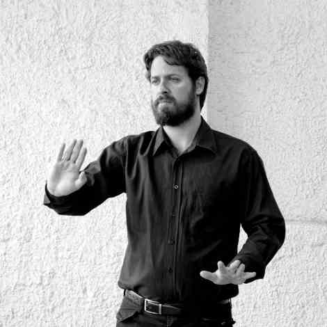 Ο Αριστείδης Ζάγκλης αναπαριστάνει την κίνηση των χεριών που δηλώνει φόβο, κατά Νεόφυτο Βάμβα.